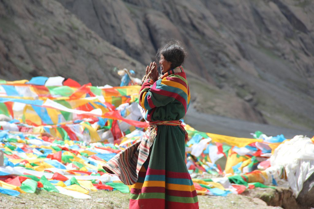 A Tibetan woman offering prayers.